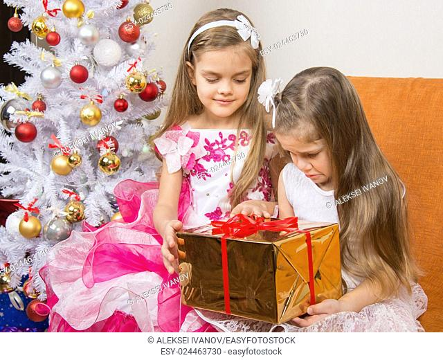 The older girl gives younger unwanted gift
