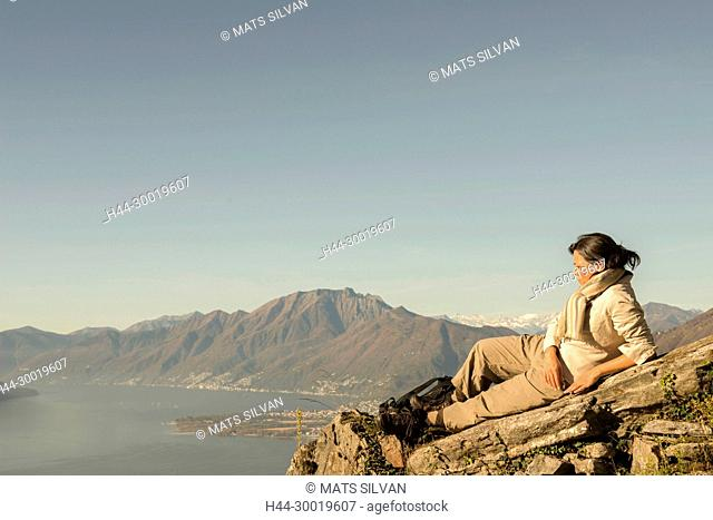 Woman Relax on a Mountain Top with Alpine Lake Maggiore in Background in Ticino, Switzerland