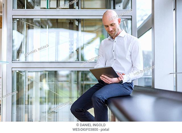 Smiling businessman sitting at the window using tablet