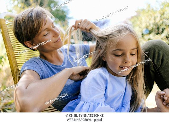 Mother braiding daughter's hair in garden