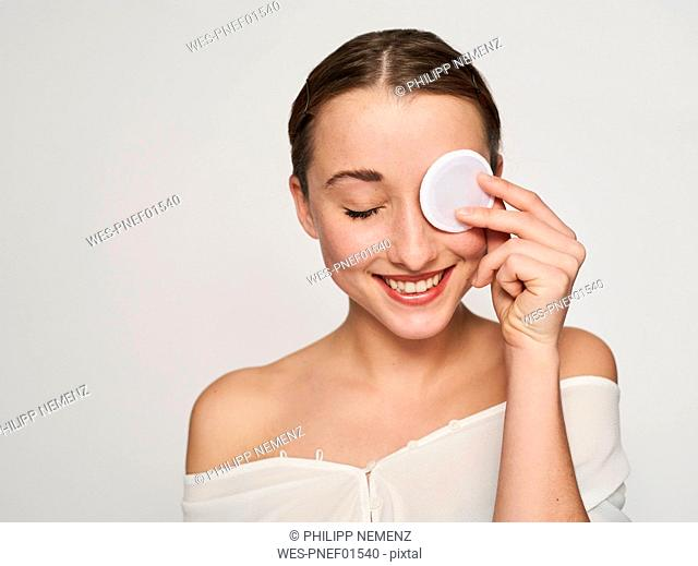 Portrait of smiling young woman with cotton pad on her eve