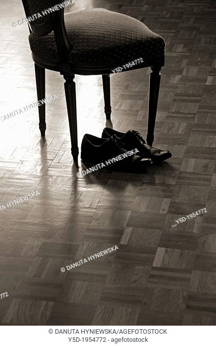 men's black shoes next to old fashioned chair, on the wooden floor, home, after work, private life