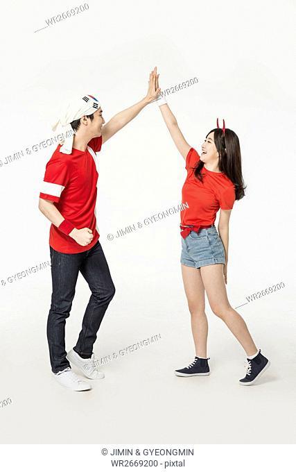 Young smiling Korean cheerleaders slapping high fives