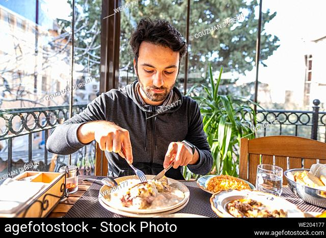 a young man uses a knife and fork on his plate for lunch in a restaurant on quarantine days