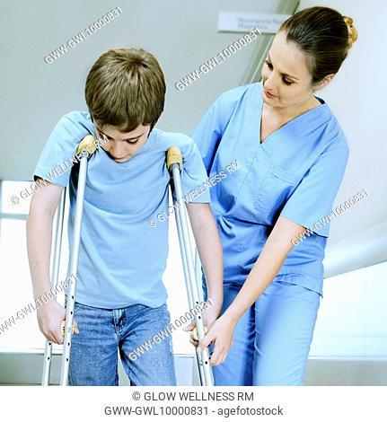 Female nurse assisting a boy on crutches