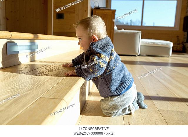 Baby boy crouching on wooden floor looking at his shadow