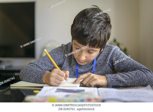 Schoolboy working on homework, Surrey, UK