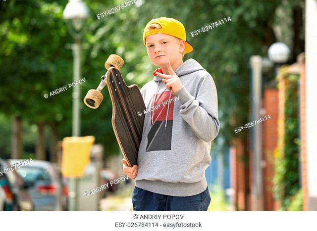 Portrait Of A Boy With Skateboard Making Peace Sign