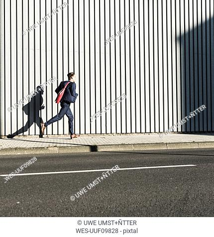Young businessman running on pavement along building
