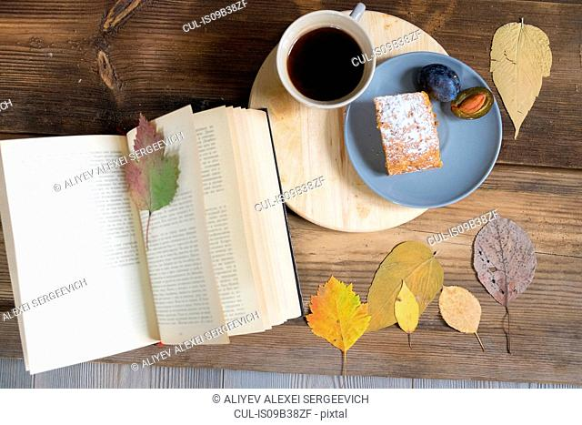Overhead view of coffee and cake with book and autumn leaves