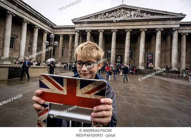 UK, London, boy standing in front of British Museum taking a selfie with his digital tablet