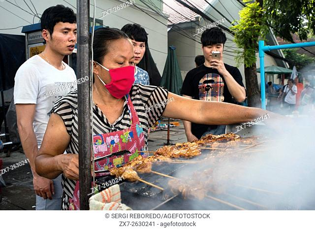 Street barbecue outside of Wha Pho temple, Bangkok, Thailand. Thai chicken barbecue offered by vendor woman. Thai street market, Bangkok
