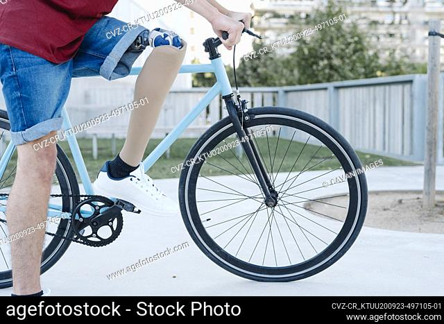 Young disabled cyclist riding bike in city