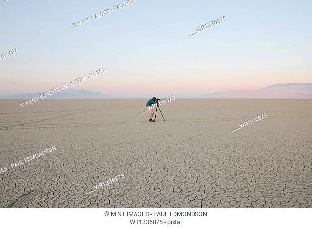 Man with camera and tripod on the flat saltpan or playa of Black Rock desert, Nevada