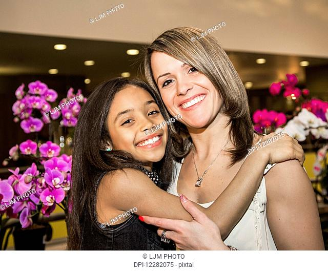 Portrait of a young mother and her daughter posing in a mall in front of flowers; St. Albert, Alberta, Canada