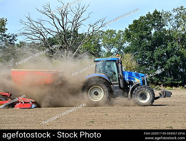 16 September 2020, Brandenburg, Schöneiche: A farmer drives a tractor with a trailed drill over a field and kicks up a lot of dust from the dry soil