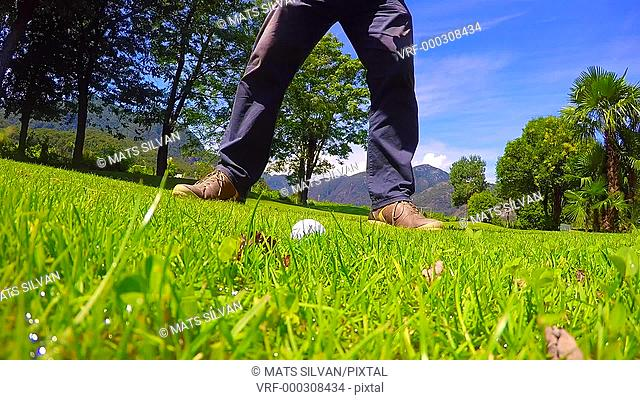 Golfer Making a Golf Swing and Hitting the Golf Ball on Wet Grass and Walking away in Ticino, Switzerland