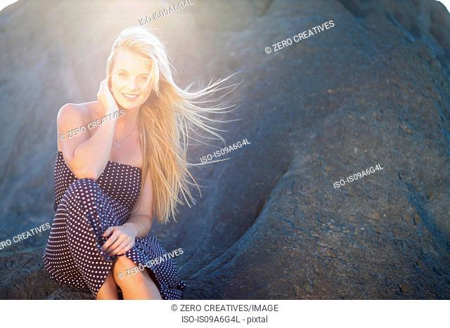 Young woman with long blonde hair sitting on rocks