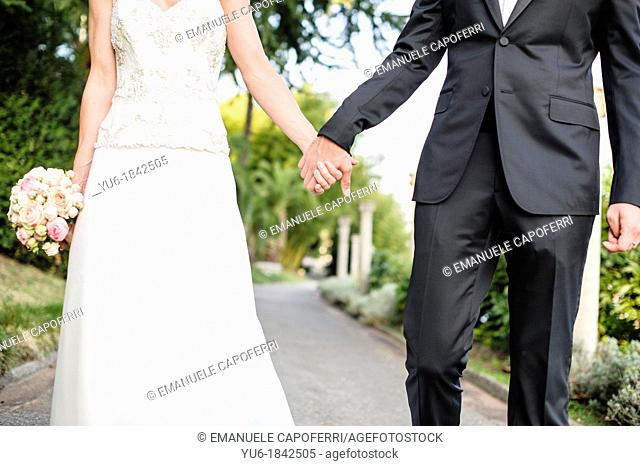 The bride and groom hold each other hands