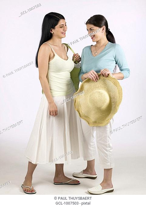 Two women with holding a sunhat and laughing