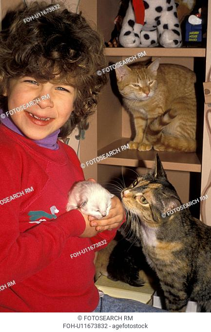 girl, cats, kitten, A mother cat looks on as a happy young girl holds a newborn kitten in her hands. Another cat sits behind on a shelf
