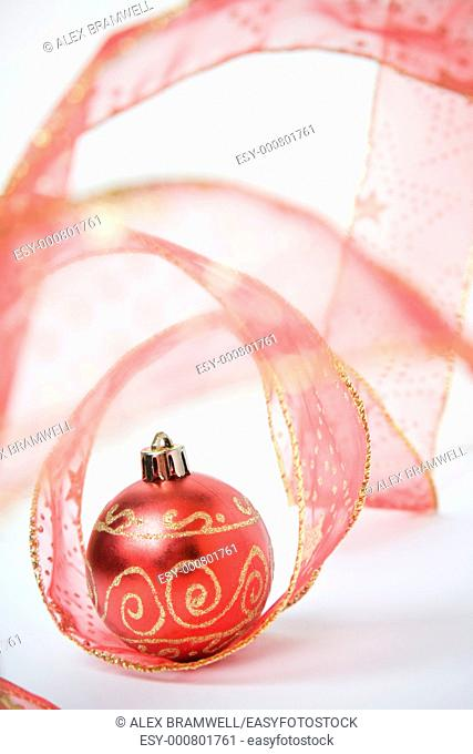 Red bauble and red ribbon over a white background