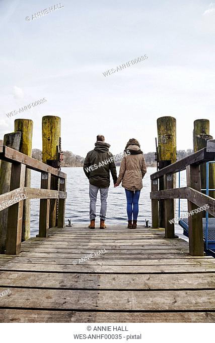 Germany, Potsdam, rear view of young couple standing on jetty at Havel River