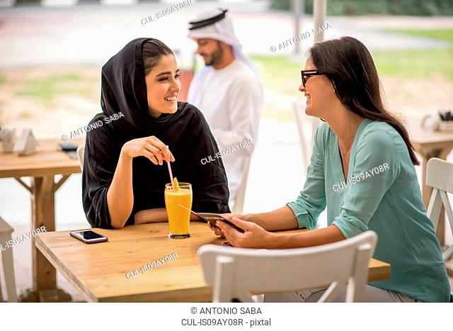 Young middle eastern woman wearing traditional clothing talking with female friend at cafe, Dubai, United Arab Emirates