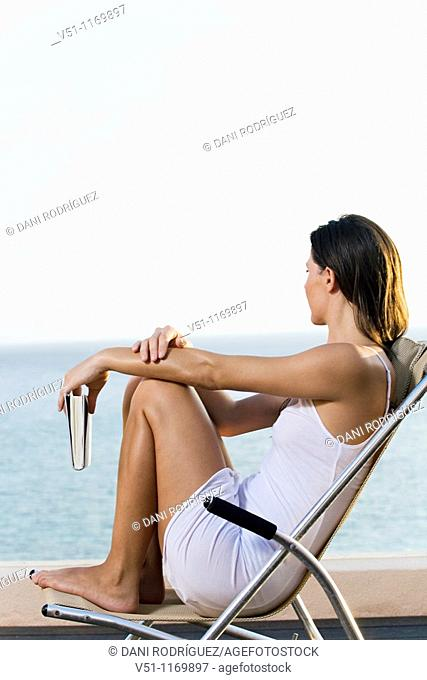 Side view of a woman looking at the ocean from a terrace with a book