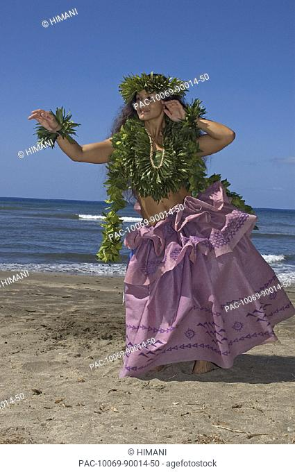Hula dancer with haku lei in traditional outfit on shoreline, ocean background