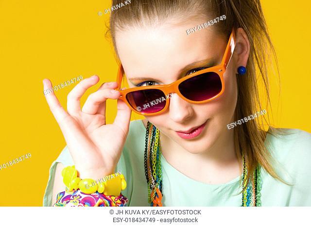 Beautiful girl wearing sunglasses, yellow background, horizon format