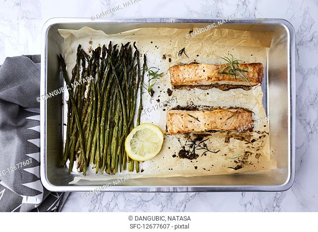 Salmon and asparagus baked in the oven, seasoned with olive oil and rosemary