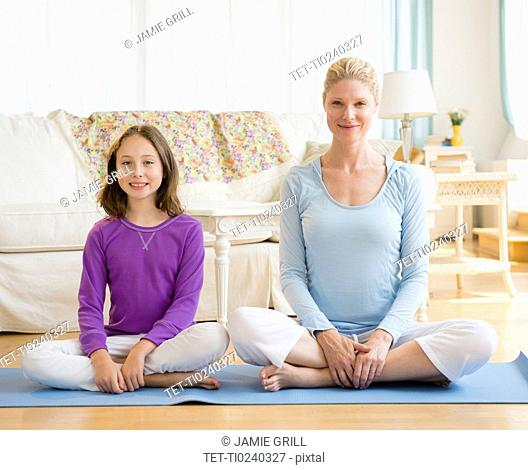 Mother and daughter 8-9 practicing yoga