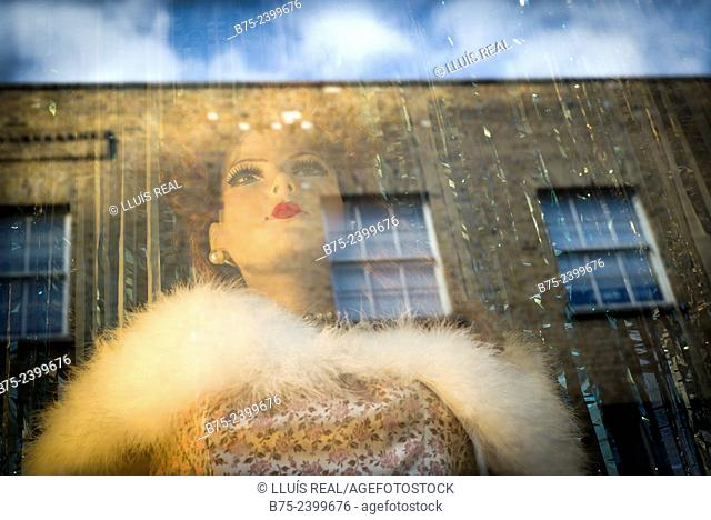 Female mannequin in a shop window and reflections in the glass of a brick building, with a blue sky and clouds. Brick Lane, East London, England, UK, Europe