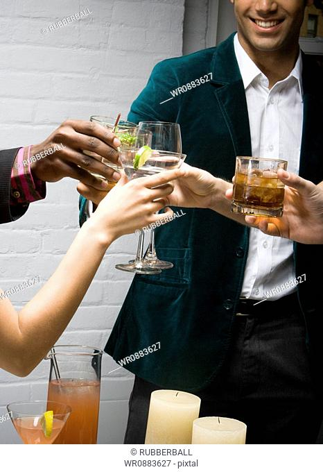 Mid section view of a man toasting drinks with his friends at a party