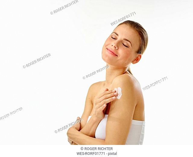 Young woman applying body creme on shoulder, closed eyes