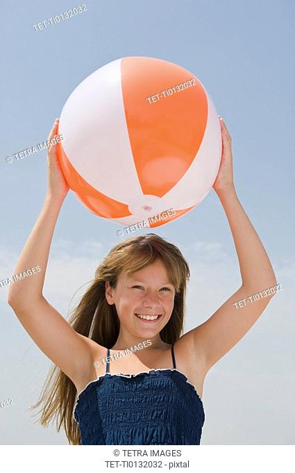 Girl holding beach ball above head