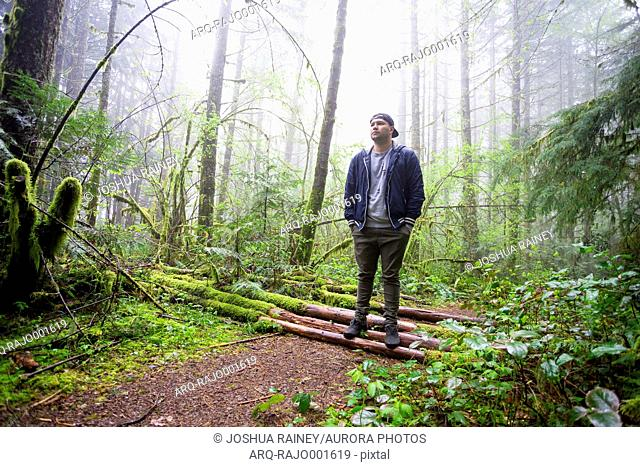 Young man standing alone with hands in pockets in mossy forest during rain and fog, Oregon, USA