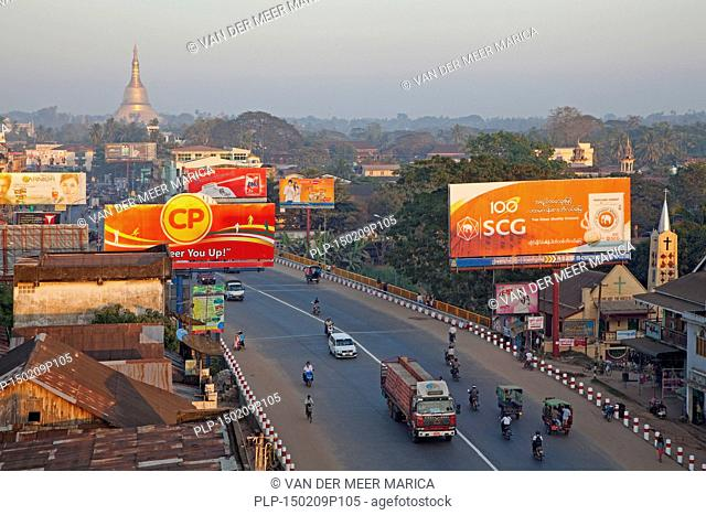 Traffic in street with billboards in the city Bago, formerly Pegu, Bago Region, Myanmar / Burma