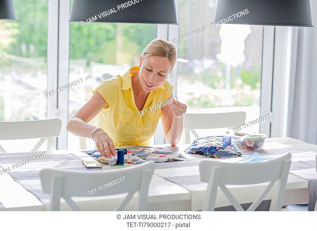 Woman making quilt