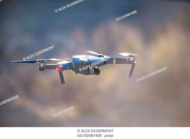 Drone (unmanned aerial vehicle) flying mid air, shallow focus