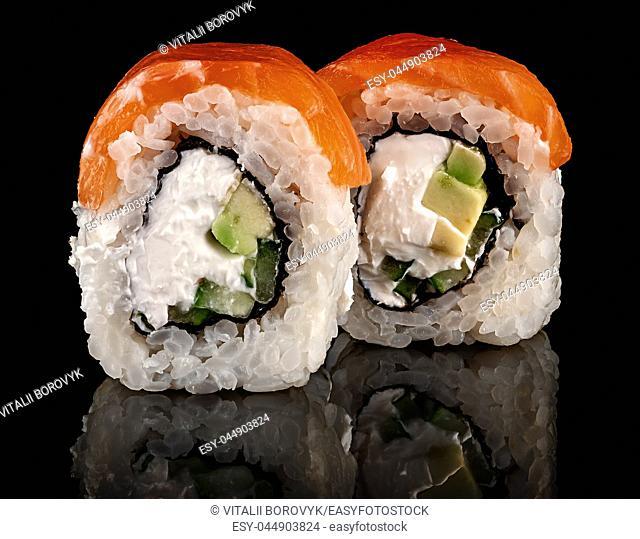Two pieces of sushi rolls Philadelphia. Black background. Reflection