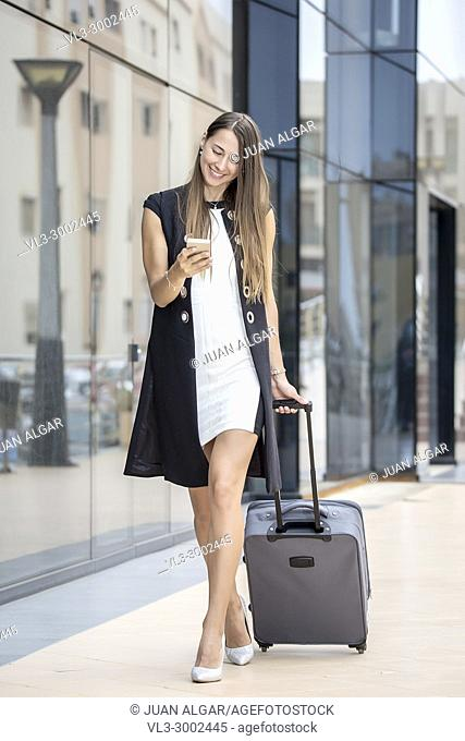 Stylish businesswoman using smartphone smilingly while walking with suitcase at street