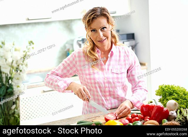 smiling woman in a shirt is slicing tomatoes on a kitchen table with vegetables