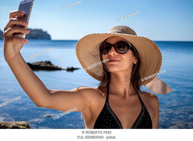 Young woman wearing sunhat on beach taking smartphone selfie, Villasimius, Sardinia, Italy