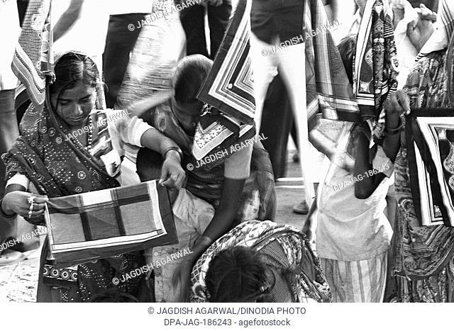 Women buying scarf Vautha fair Gujarat India Asia 1983