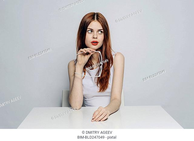 Curious Caucasian woman sitting at table holding white eyeglasses