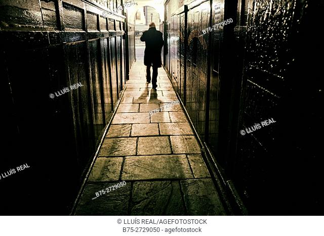 Silhouette of unrecognizable man walking at night through a hallway, wearing black coat. London, England