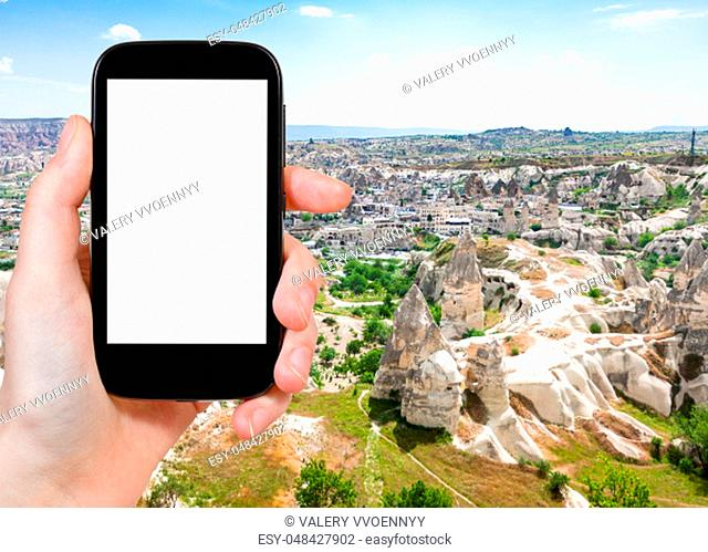 travel concept - tourist photographs of carved houses and Goreme town from mountain in Cappadocia in spring in Turkey on smartphone with empty cutout screen...