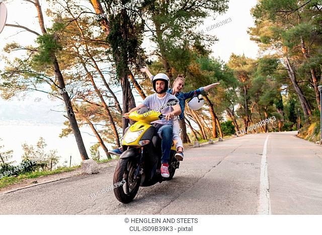 Couples riding moped on rural road, Split, Dalmatia, Croatia